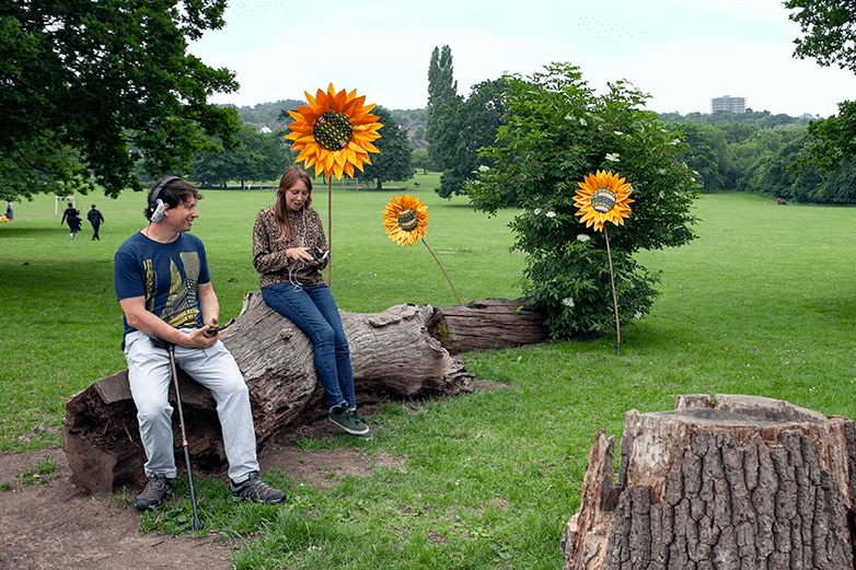 Two people sit on a large tree trunk in a park with large fake sunflowers behind them. They both have headphones on and are listening to something.
