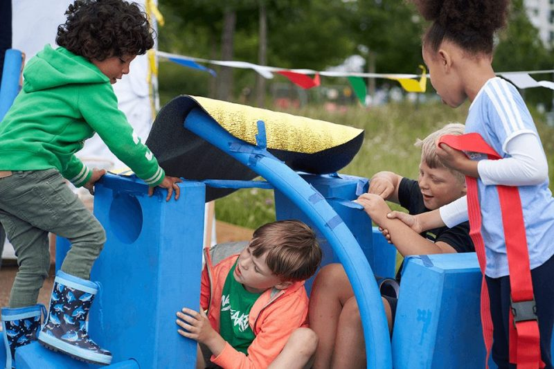 4 children playing on a large blue strucure outside in a large green space